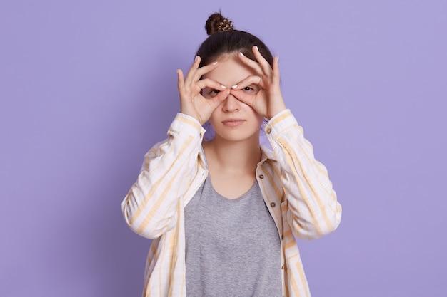 Hübsche junge frau mit verärgertem gesicht, das finger nahe augen wie brille hält