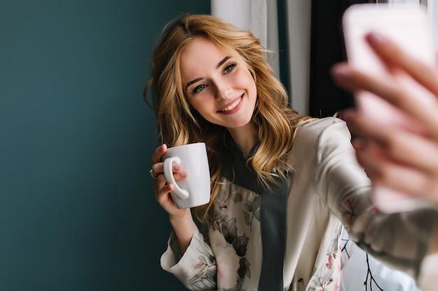 Hübsche junge frau mit welligem blondem haar, das selfie nimmt, das neben dem fenster mit tasse kaffee des morgens, tee sitzt. sie trägt einen seidenpyjama. türkisfarbene wand.