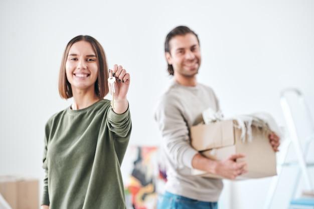Hübsche junge frau mit zahnigem lächeln, das ihnen schlüssel von der neuen wohnung oder vom neuen haus zeigt, nachdem sie entfernt wird, während ihr ehemann mit kiste nahe steht