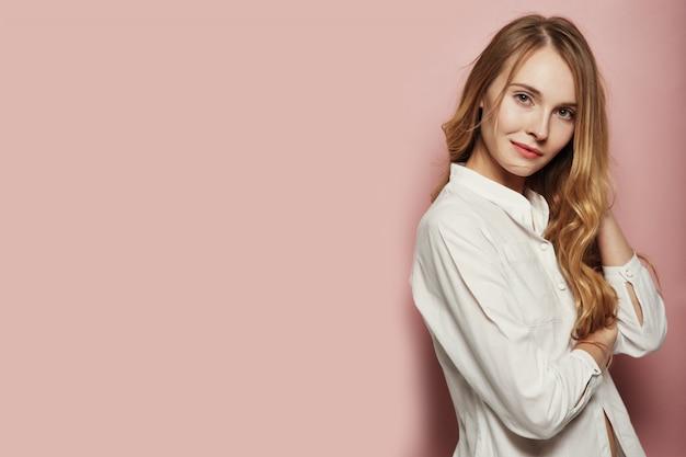 Hübsche junge frau posiert auf rosa hintergrund