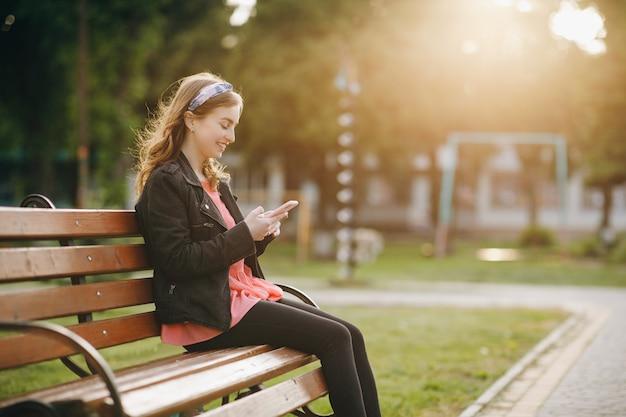 Hübsche junge frau sitzt auf einer bank im stadtpark und schreibt aktiv nachrichten über ihr telefon