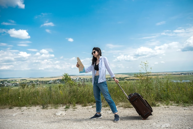Hübsche junge frau stehen und schauen auf die karte auf der straße, genießen sie sommerferien in der natur