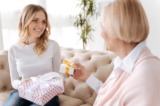 Hübsche junge frau und ihre ältere mutter sitzen auf dem sofa und verteilen sich gegenseitig geschenkboxen, während sie sich liebevoll ansehen