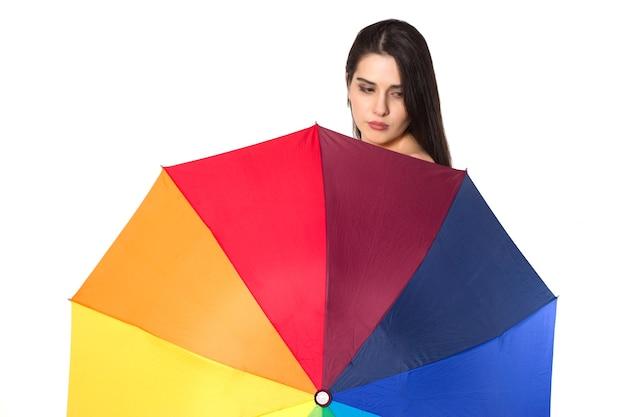 Hübsche junge frau unter buntem regenschirm, isoliert auf weißem hintergrund