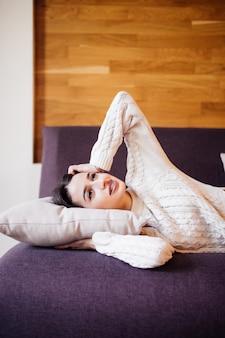 Hübsche junge frau wachte nach einem täglichen nickerchen zwischen den arbeiten auf dem dunklen sofa in ihrer wohnung auf