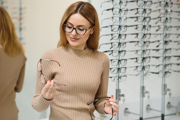 Hübsche junge frau wählt neue brille im optikgeschäft