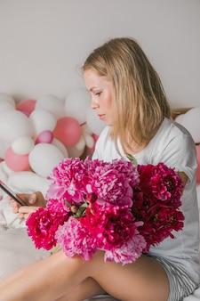 Hübsche junge frau zu hause im schlafzimmer im bett mit blumen macht ein selfie mit dem handy