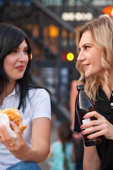 Hübsche junge frauen essen hamburger im freien auf der straße.