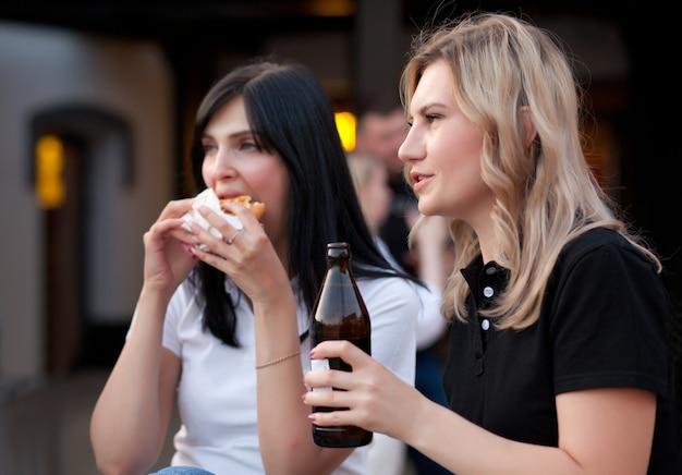 Hübsche junge frauen essen hamburger und trinken bier im freien auf der straße