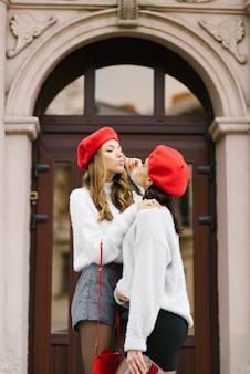 Hübsche junge frauen in baskenmützen blasen sich gegenseitig einen kuss