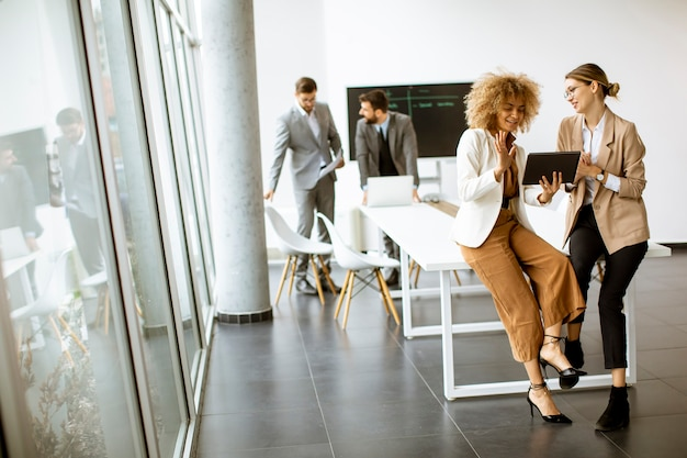 Hübsche junge frauen mit digitalem tablet im modernen büro vor ihrem team