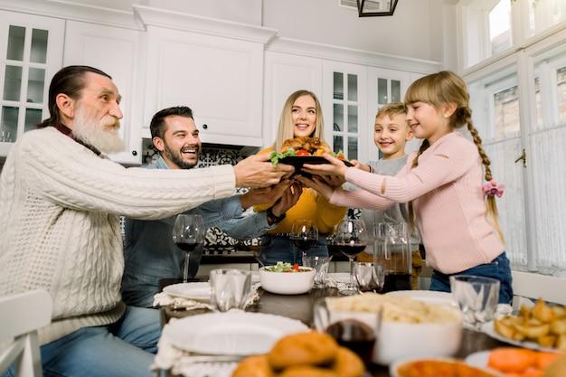 Hübsche junge fraumutter mit köstlichem truthahn für feiertagsdinner mit familie