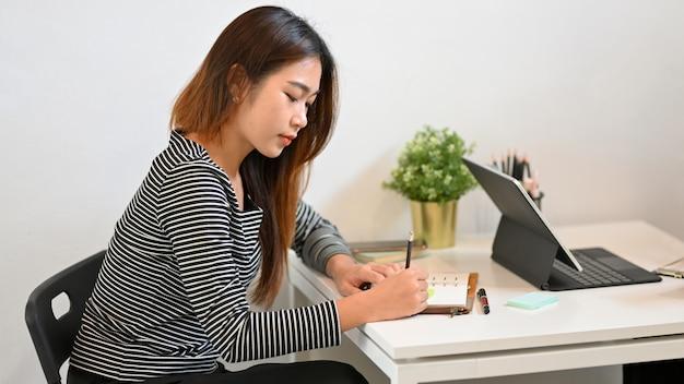 Hübsche junge freiberuflerin, die im café sitzt, arbeitet und sich notizen zum stundenplan macht