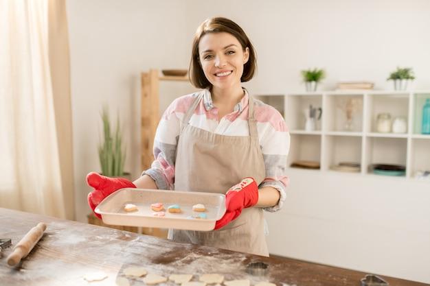 Hübsche junge fröhliche frau in der schürze und in den schutzhandschuhen, die heißes tablett mit hausgemachten keksen halten