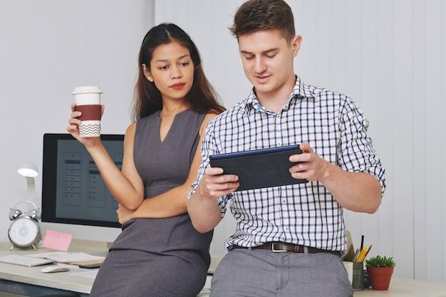 Hübsche junge gemischtrassige geschäftsfrau, die kaffee trinkt und bildschirm in der hand ihres kollegen auf tablet-computer betrachtet