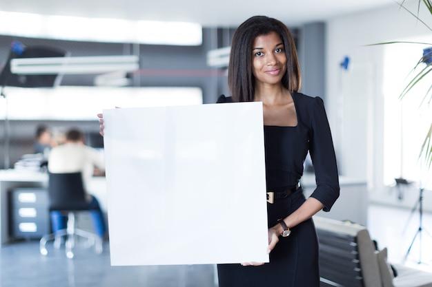 Hübsche, junge geschäftsdame im leeren papier des schwarzen starken reihengriffs