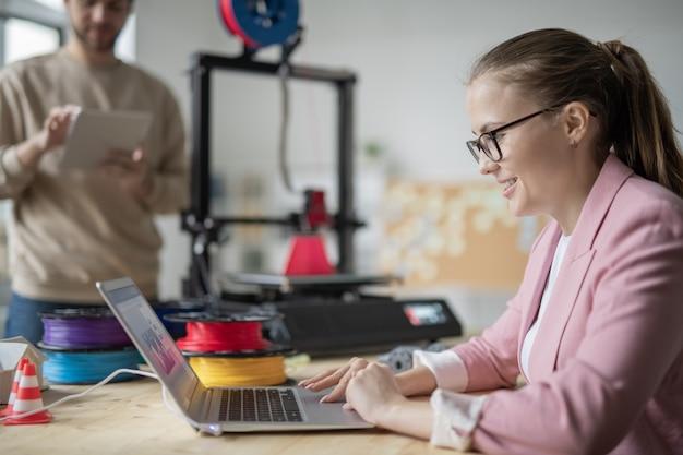 Hübsche junge geschäftsfrau, die laptopanzeige beim arbeiten mit elektronischen skizzen von geometrischen figuren vor dem drucken betrachtet