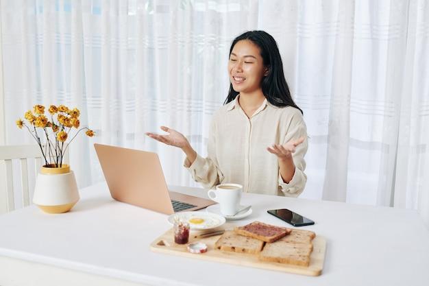 Hübsche junge geschäftsfrau, die mit frühstück an ihrem tisch sitzt und online-treffen mit kollegin hat