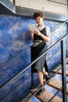Hübsche junge geschäftsfrau, die mobiles drahtloses gerät benutzt, während sie sich unten im bürogebäude bewegt