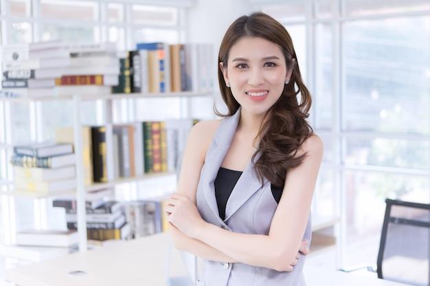 Hübsche junge geschäftsfrau, erfolgreiches vertrauen mit verschränkten armen im büroraum.