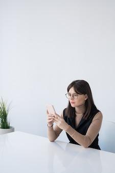 Hübsche junge geschäftsfrau im intelligenten lässigen scrollen im smartphone beim sitzen am schreibtisch gegen weiße wand im büro