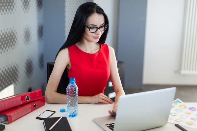 Hübsche, junge geschäftsfrau in rotem kleid und brille sitzen am tisch und arbeiten