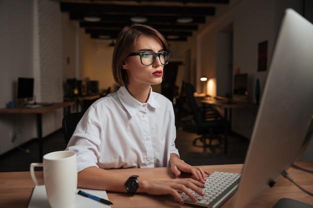 Hübsche junge geschäftsfrau mit brille, die im büro am computer arbeitet und tippt