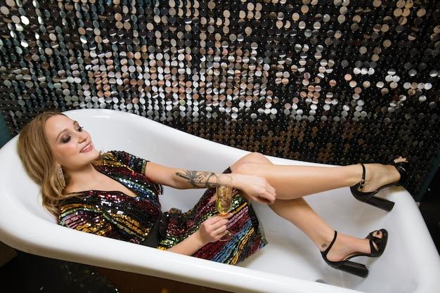 Hübsche junge glamouröse frau, die mit champagnerflöte aufmuntert, während sie in der leeren badewanne liegt, während party genießt