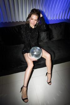 Hübsche junge glamouröse frau mit discokugel, die auf schwarzer weicher samtcouch sitzt und party im nachtclub genießt