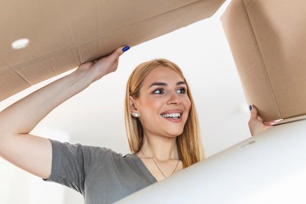 Hübsche junge glückliche frau, die einen kartonkasten öffnet. frau, die beim öffnen der schachtel überrascht in ein weihnachtsgeschenk schaut.