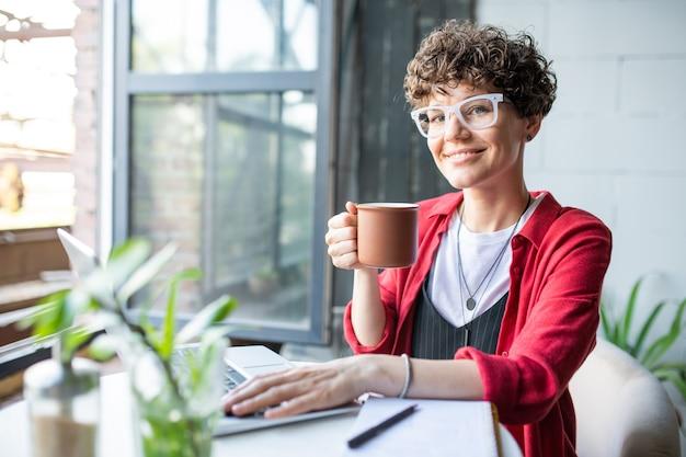 Hübsche junge glückliche frau in der intelligenten freizeitkleidung, die sie beim tee oder kaffee betrachtet und laptop im café verwendet