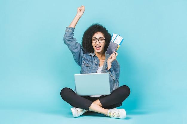 Hübsche junge glückliche schwarze afroamerikanerfrau, die auf dem boden mit laptop und flugtickets lokalisiert über blauem hintergrund sitzt. gewinner.
