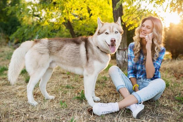 Hübsche junge hübsche lächelnde glückliche blonde frau, die mit hund husky rasse im park am sonnigen sommertag spielt