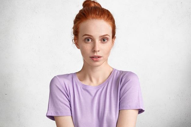 Hübsche junge ingwerfrau mit haarknoten, gekleidet in hellem lässigem lila t-shirt, sieht selbstbewusst aus