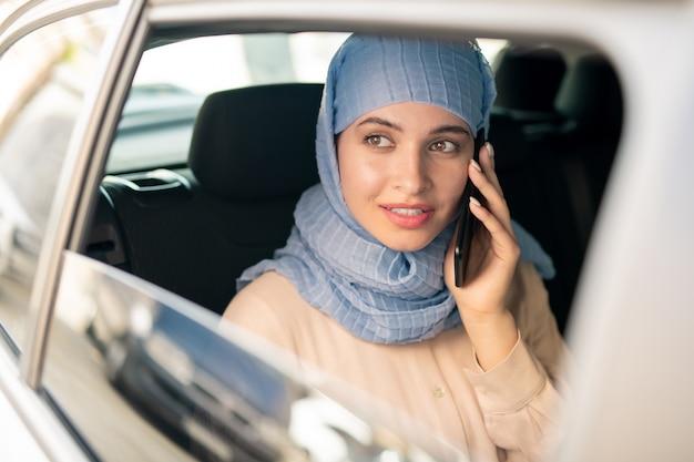 Hübsche junge islamische geschäftsfrau im hijab, die auf smartphone spricht, während sie morgens mit dem taxi zur arbeit geht