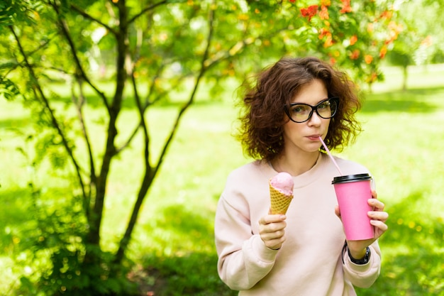 Hübsche junge kaukasische frau gehen im park spazieren, trinkt kaffee und isst eis