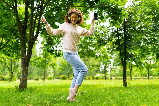 Hübsche junge kaukasische frau gehen im park spazieren und hört musik und tänze