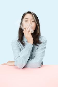 Hübsche junge koreanische frauen, die zigarre rauchen, während sie am tisch im studio sitzen.