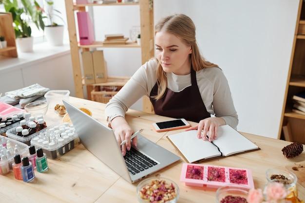 Hübsche junge kreative frau in der schürze, die am arbeitsplatz vor laptop sitzt, während notizen über ihr hobby macht