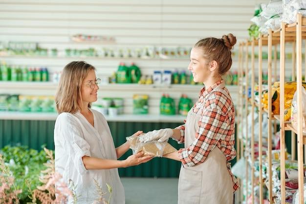 Hübsche junge lächelnde arbeiterin des gewächshauses, die ihrer reifen kollegin zwei packungen granulierten dünger für das wachstum von pflanzen übergibt