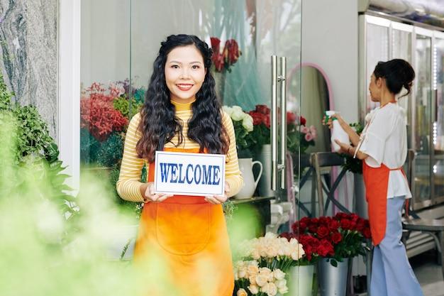 Hübsche junge lächelnde blumenladenbesitzerin, die kunden innen begrüßt, ihre kollegin, die blumen sprüht