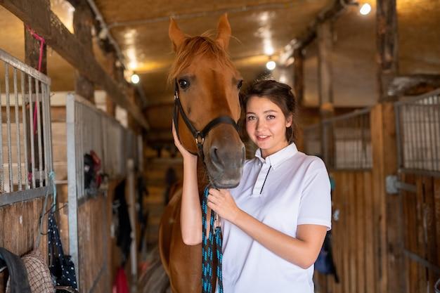 Hübsche junge lächelnde brünette, die eine hand durch die schnauze der reinrassigen braunen stute hält, während sie im stall steht