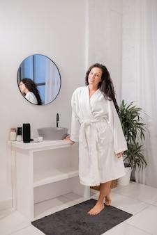 Hübsche junge lächelnde brünette frau im weißen bademantel, die auf kleinem teppich vor kamera im badezimmer steht