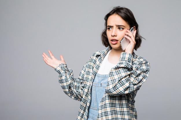 Hübsche junge lächelnde frau, die am telefon spricht