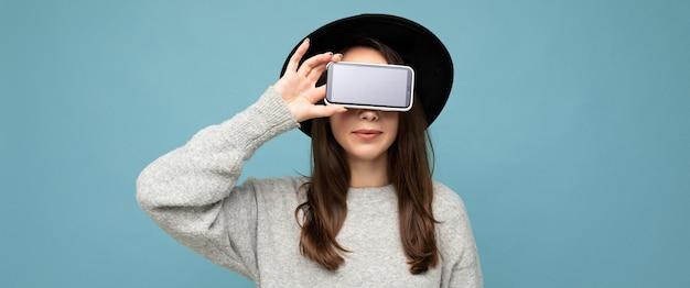 Hübsche junge lächelnde frau, die schwarzen hut und grauen pullover hält telefon hält kamera