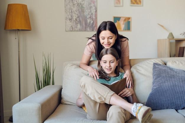 Hübsche junge lächelnde frau mit ihrem kinn auf dem kopf einer klugen tochter im teenageralter mit offenem buch, das zusammen liest, während sie zu hause bleibt