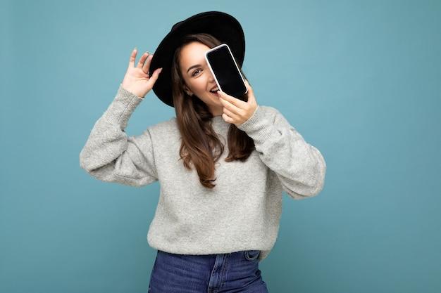 Hübsche junge lächelnde frau mit schwarzem hut und grauem pullover, die das telefon mit blick auf die kamera im hintergrund hält. mock-up, ausschnitt, freier raum. platz kopieren