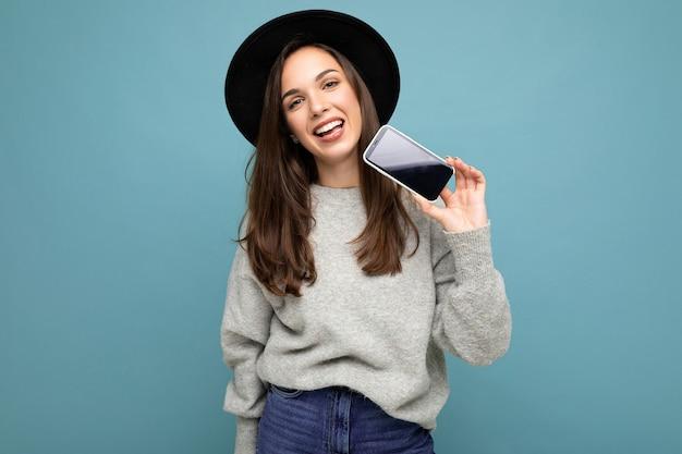 Hübsche junge lächelnde frau mit schwarzem hut und grauem pullover, die das telefon mit blick auf die kamera im hintergrund hält. mock-up, ausschnitt, leerer raum