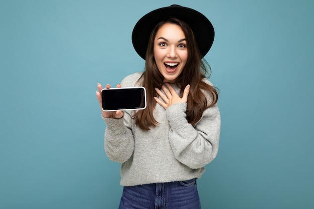 Hübsche junge lächelnde frau mit schwarzem hut und grauem pullover, die das telefon mit blick auf die kamera im hintergrund hält.
