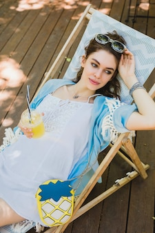 Hübsche junge lächelnde stilvolle frau, die im sommer-outfit im liegestuhl sitzt und weißes kleid, blauen umhang, sonnenbrille, geldbörse trägt, frischen saft trinkt und sich entspannt